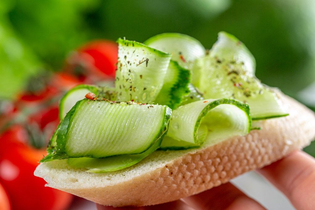 Sandwich with fresh sliced cucumber in hand close-up (Flip 2019)