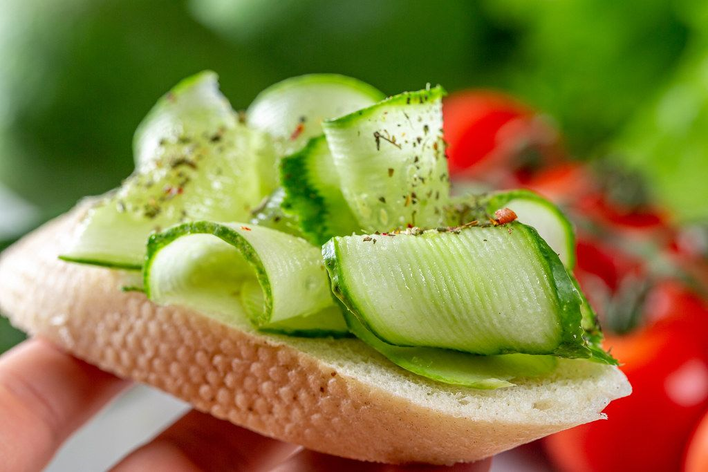 Sandwich with fresh sliced cucumber in hand close-up