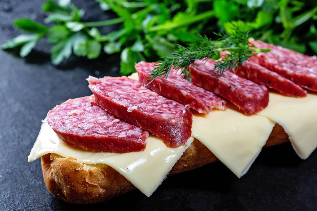 Sandwich with salami and cheese on black background