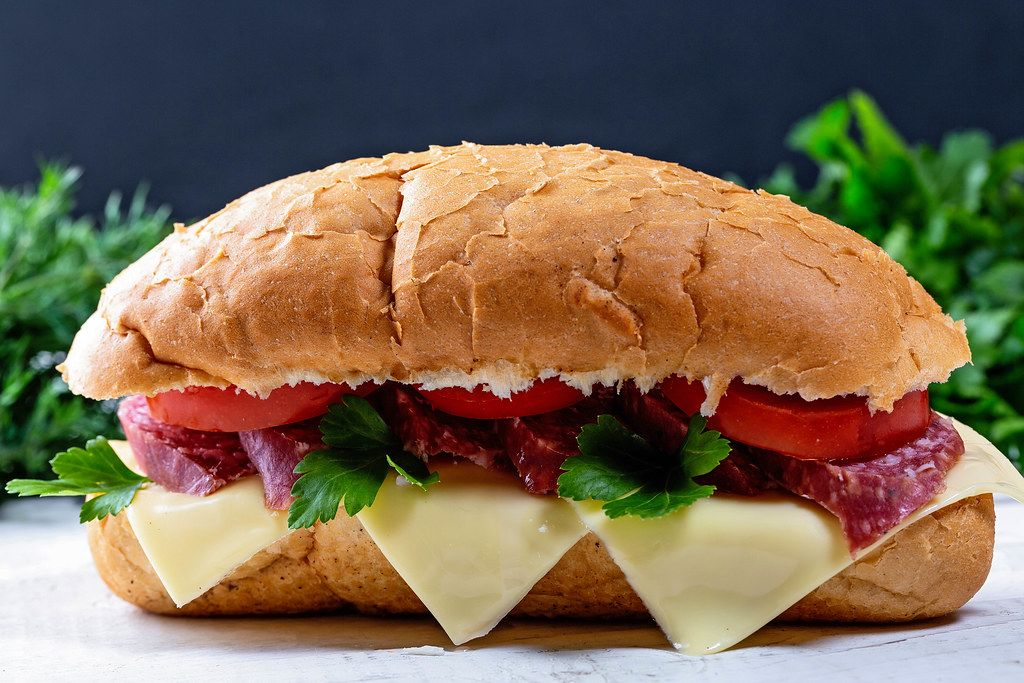 Sandwich with salami, tomatoes, cheese and herbs
