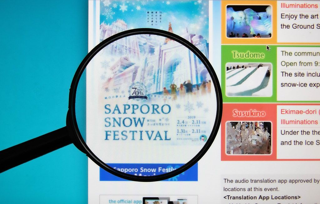 Sapporo Snow Festival text on a computer screen with a magnifying glass