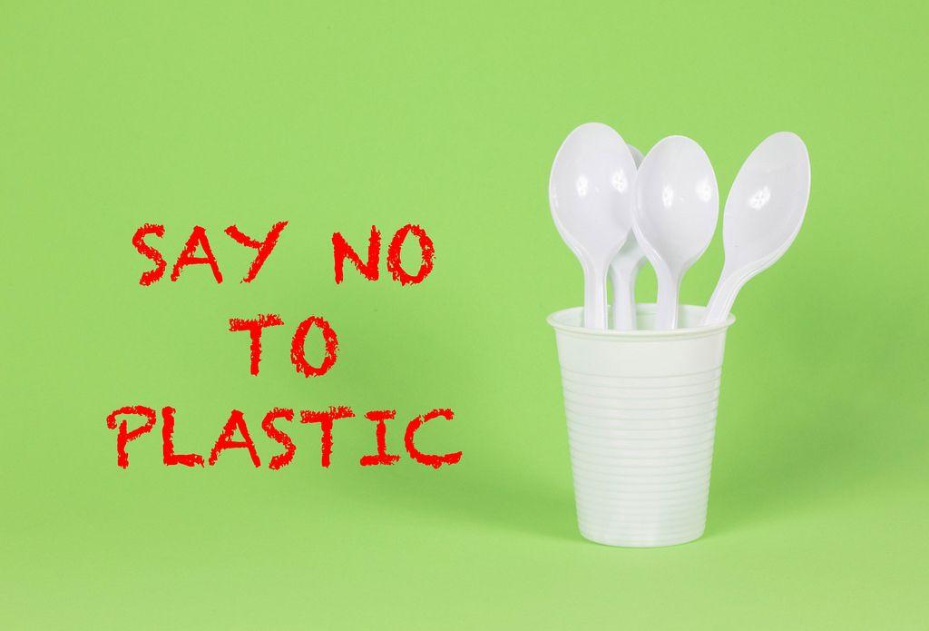 Say No To Plastic - Plastiklöffel im Becher auf grünem Hintergrund