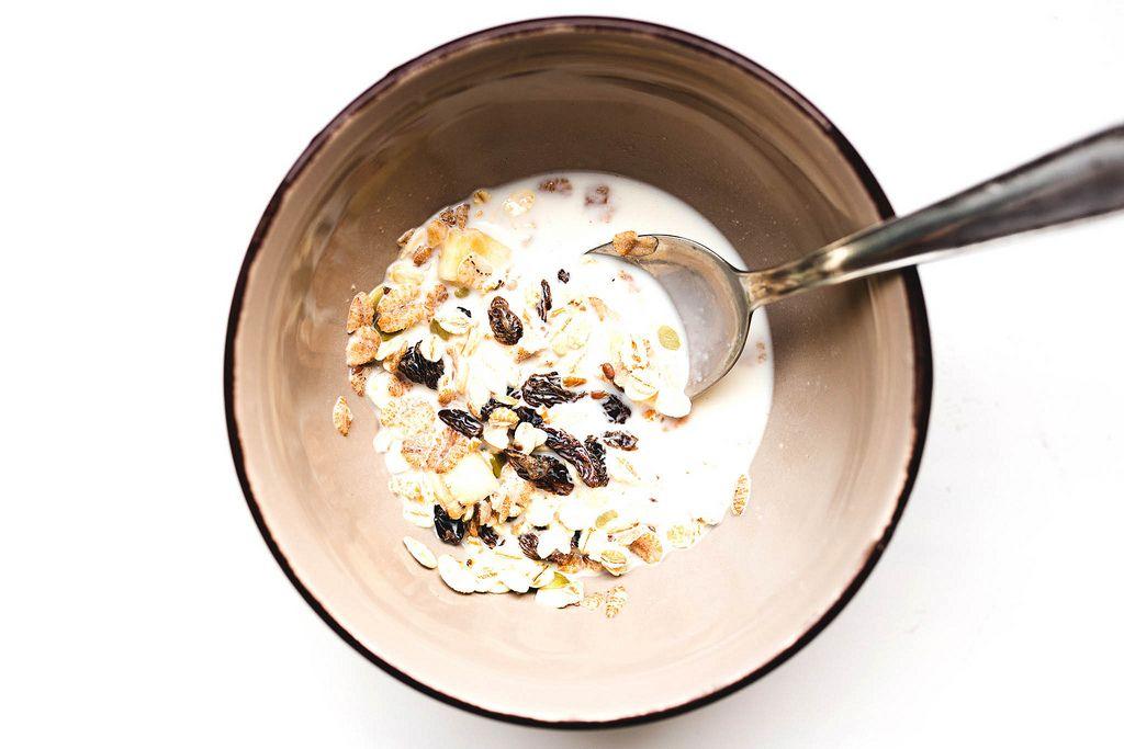 Schale gefüllt mit Haferflockenmüsli mit Rosinen und Milch auf weißem Hintergrund