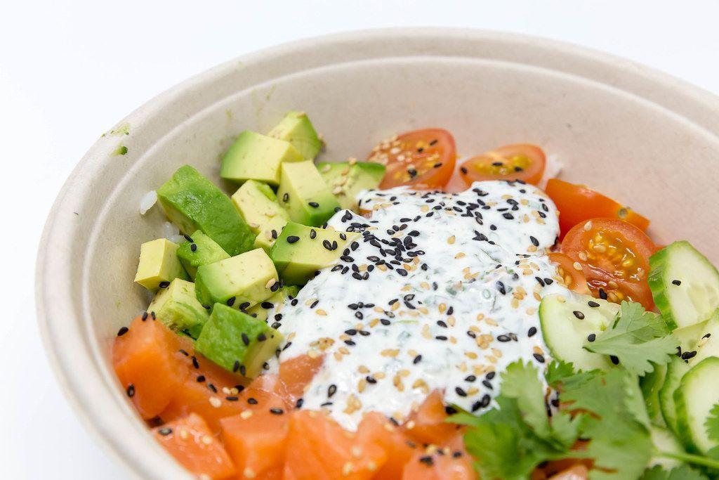 Schale mit geschnittenen Tomaten, Avocado, Gurken, verfeinert mit Petersilie, Joghurt und gesunden Samen