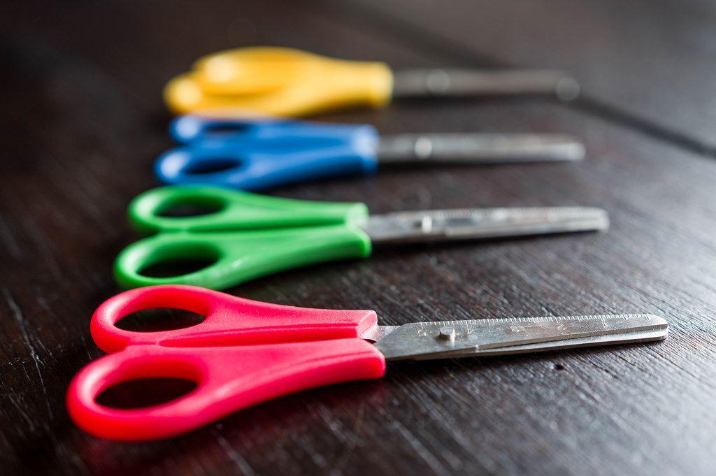 Scheren in verschiedenen Farben auf einem Holztisch