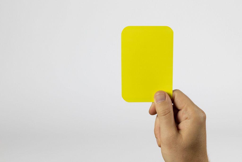 Schiedsrichter zeigt gelbe Karte