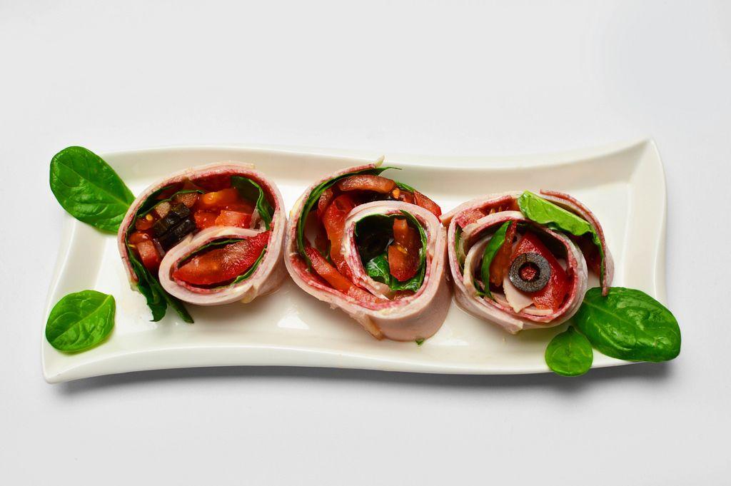 Schinken-Gemüse Röllchen mit Tomaten und Oliven in der Aufsicht