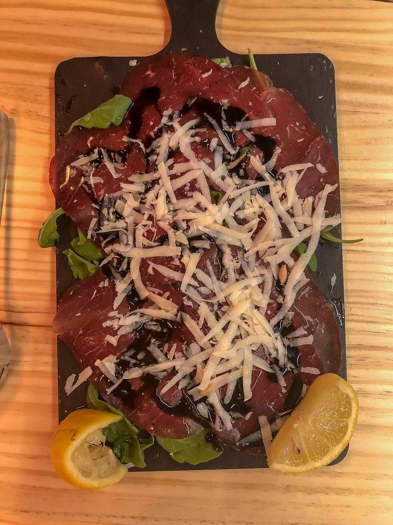 Schinken mit geriebenem Parmesan Käse auf Rucolabett mit Zitrone und Balsamico Essig auf einem schwarzen Brettchen