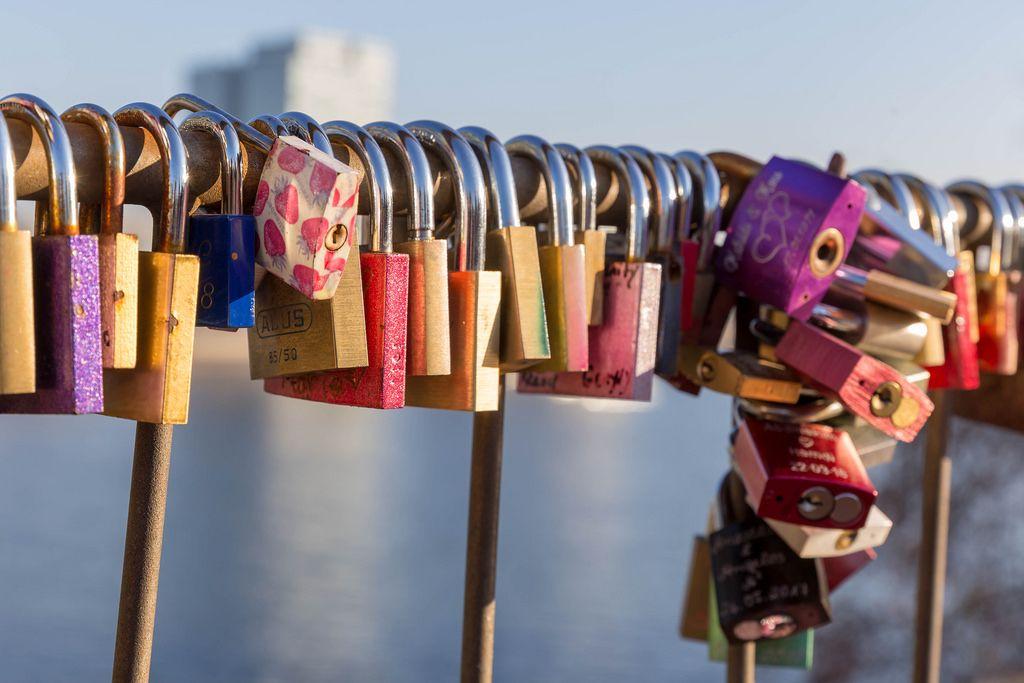 Schlösser hängen als Beweis der Liebe an einer Brücke in Köln