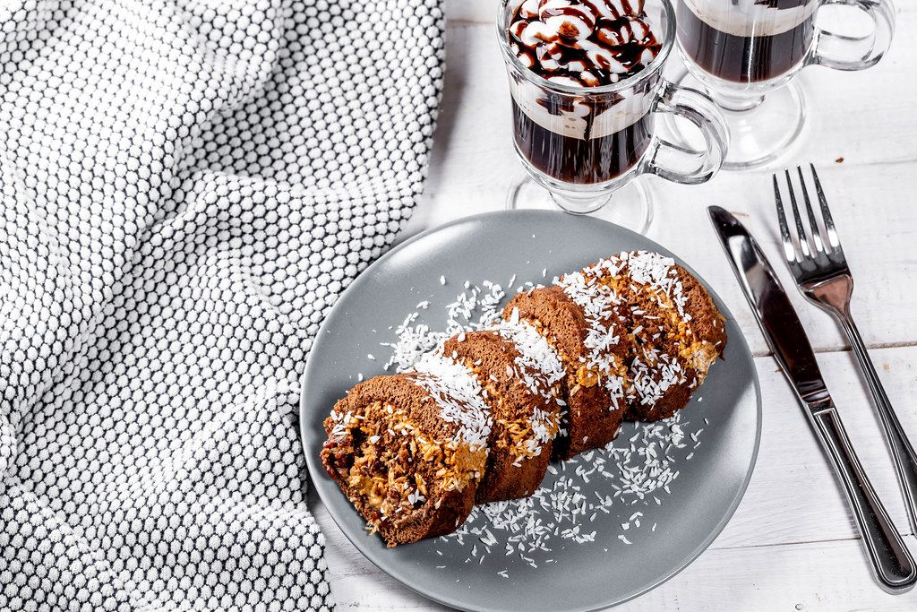 Schokoladen-Biskuit-Rolle mit Kokosraspeln, neben einem Kaffee, auf einem weißen Tisch im Landhausstil
