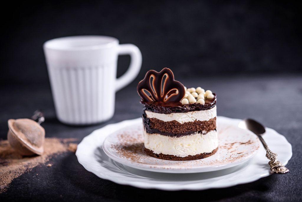 Schokoladen-Sahnekuchen mit artistischem Dekor auf weißem Teller und schwarzem Hintergrund