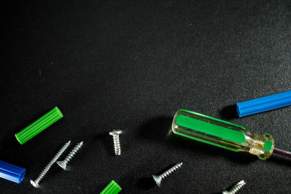 Schrauben und Werkzeuge auf einer schwarzen Oberfläche