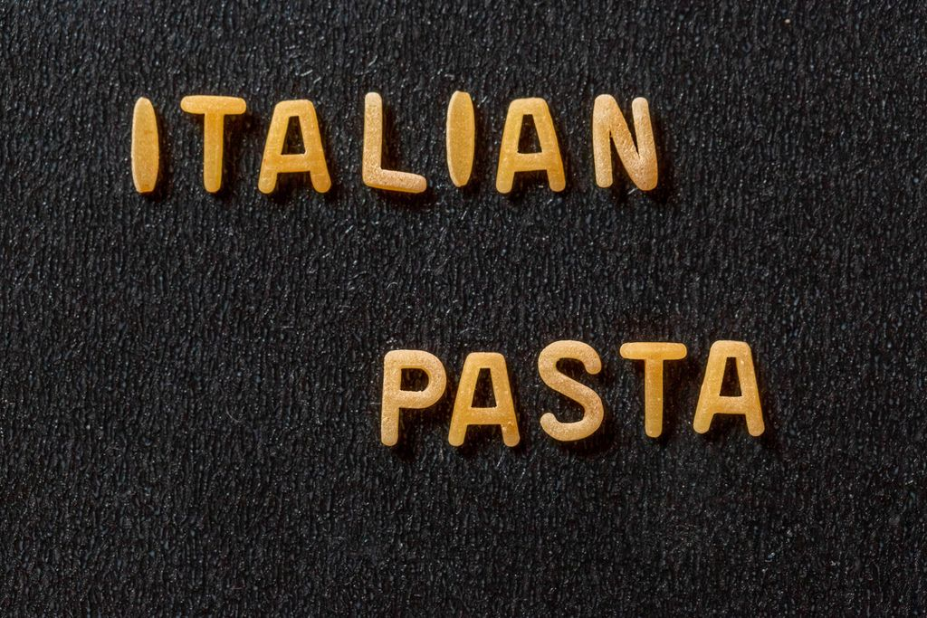 Schriftzug Italian Pasta aus Nudeln auf schwarzem Hintergrund