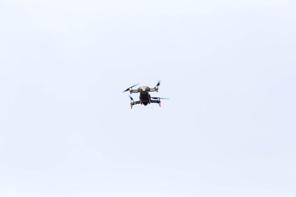 Schwarze Drohne mit vier Propellern fliegt am Himmel