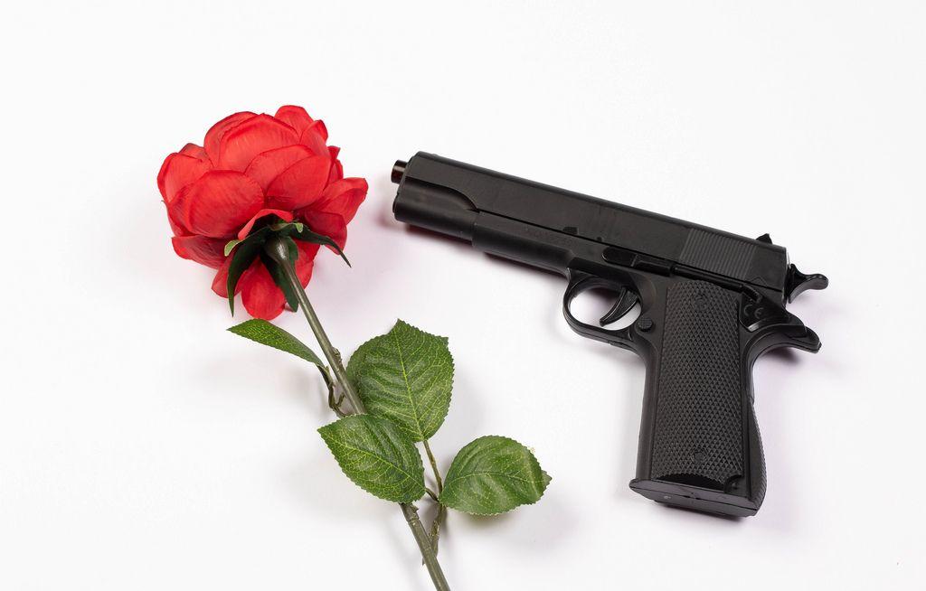 Schwarze Handfeuerwaffe neben einzelner roter Rose vor weißem Hintergrund