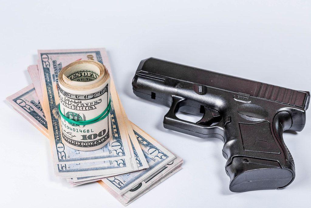 Schwarze Waffe und Geld in Dollarnoten auf einem weißen Hintergrund