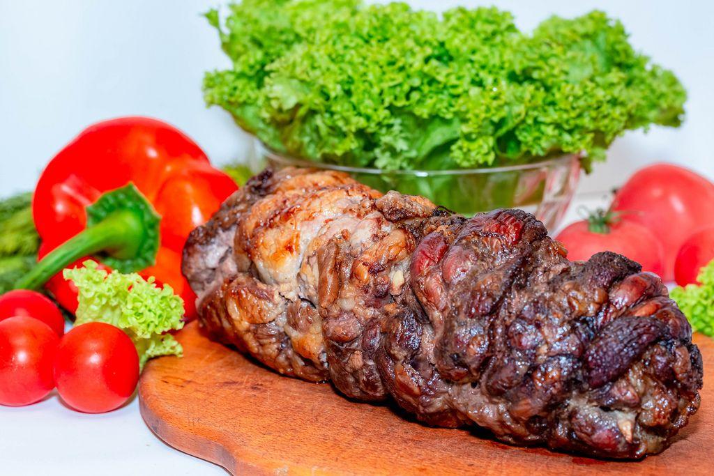 Schweineroulade mit Gemüse wie Tomaten und Paprika auf Küchenbrett mit Kraussalat