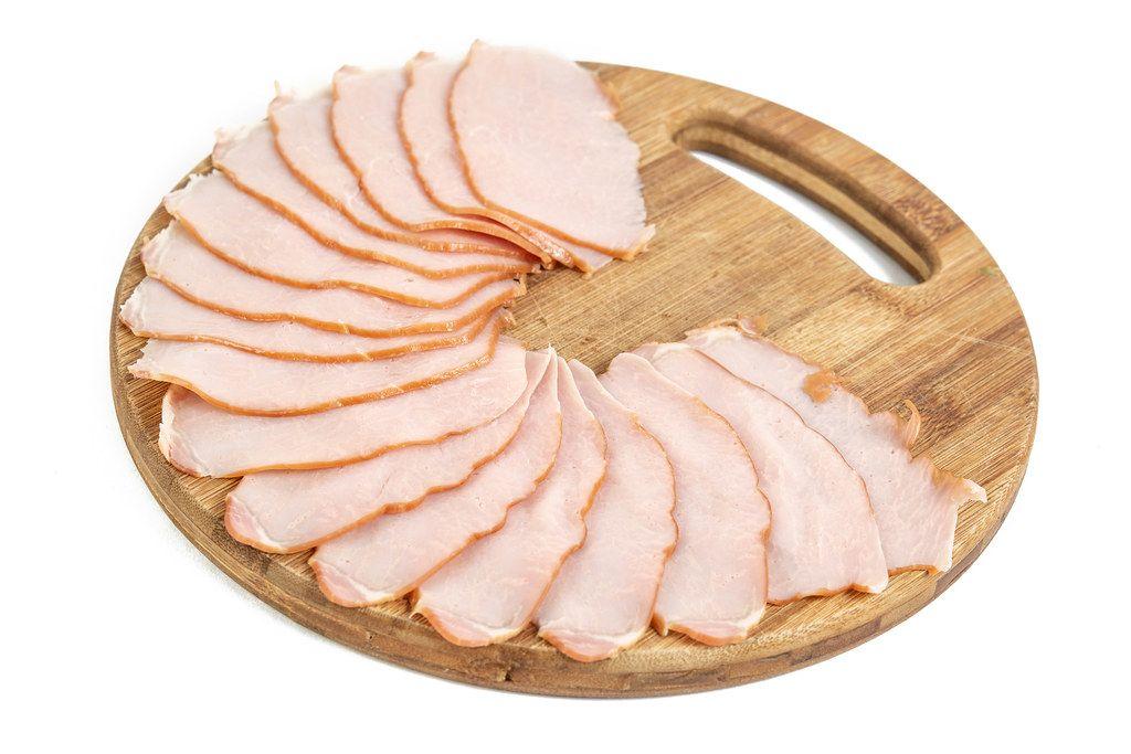 Schweineschinken auf rundem Holzbrett für die Brotzeit arrangiert