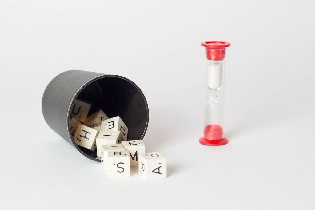 Scrabble-Würfel im Becher und eine Sanduhr