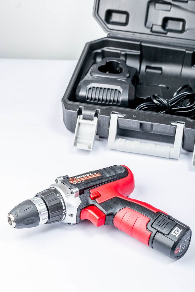 Screwdriver on white background and tool box behind