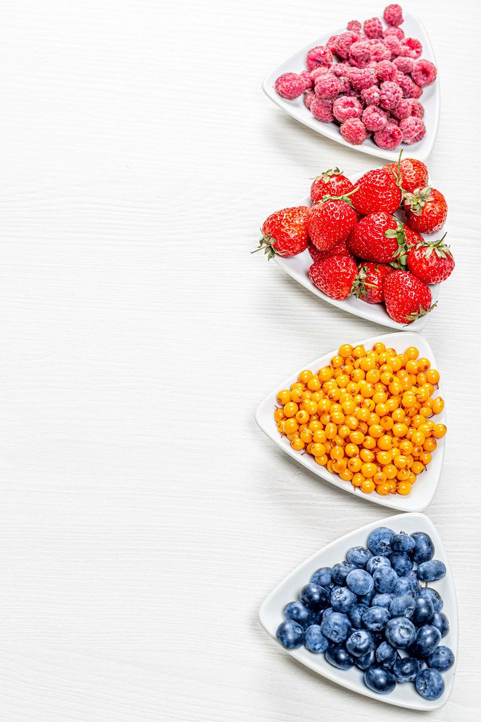 Sea buckthorn, blueberries, raspberries and strawberries on white wooden background