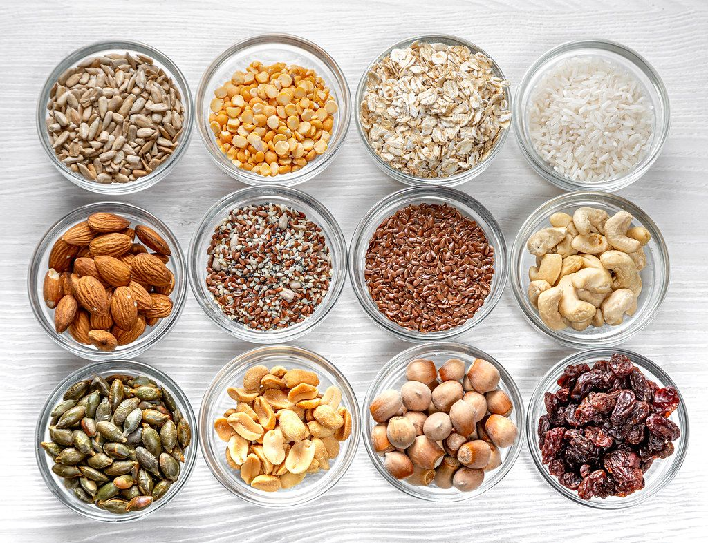 Seeds, nuts, grains in glass bowls on a white wooden background. Top view