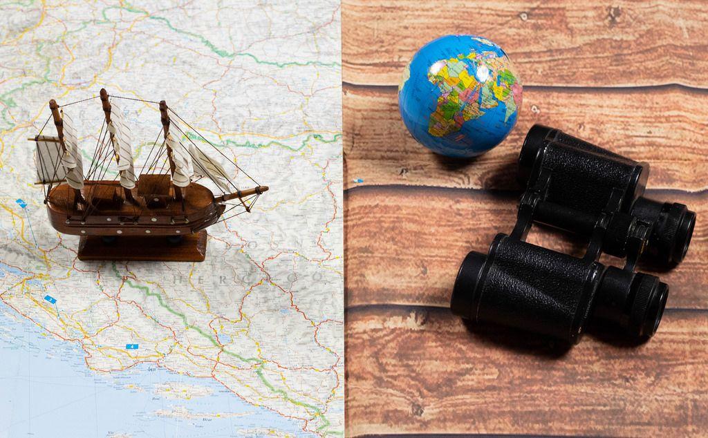 Segelschiff auf landkarte und fernglas mit globus als symbolbild