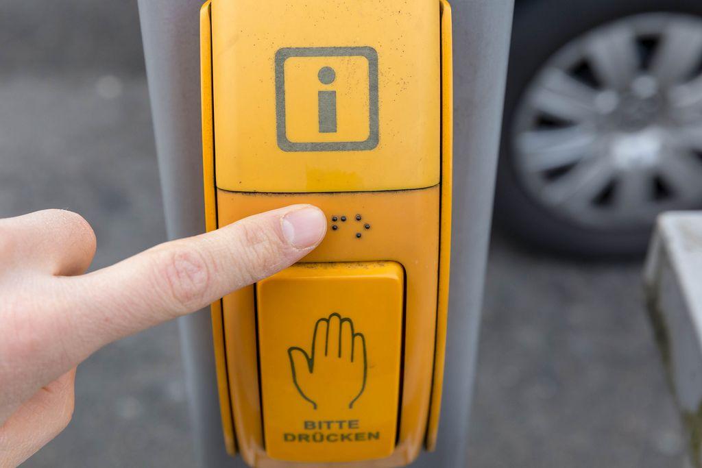Sehbehinderter Fußgänger liest Blindenschrift an gelbem Druckknopf für Ampelanlage in Köln