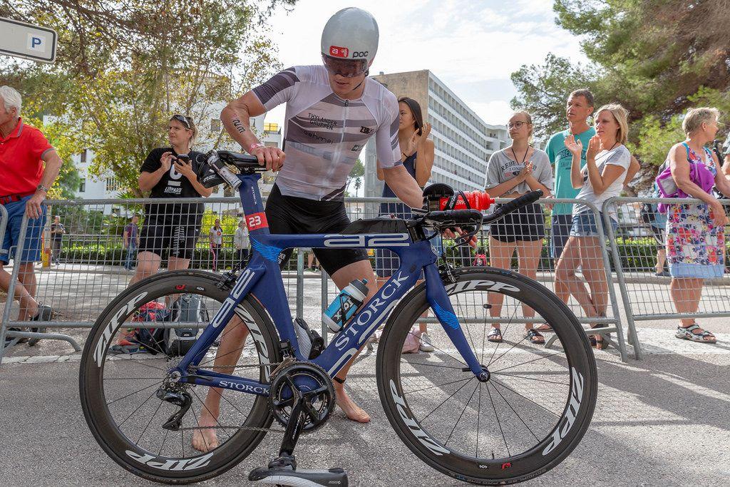 Seitenansicht eines Athleten mit der Nummer 23 beim Challenge Triathlon der sich auf ein blaues Rennrad aufsetzt