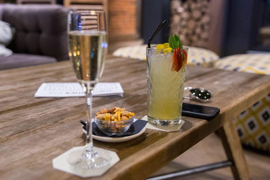 Sekt,Cocktail, Handy und kleine Schale Nüsse auf einem rustikalen Holztisch in der Lounge und Bar des The Corner Hotels in Barcelona, Spanien