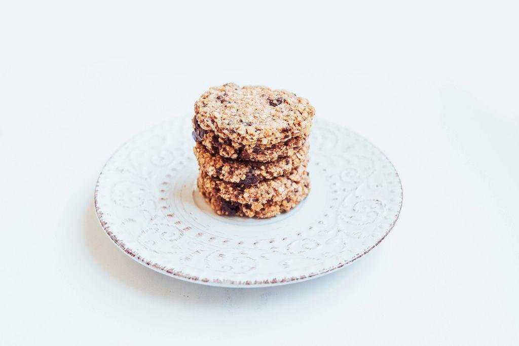 Selbst gemachte Haferkekse mit Schokolade gestapelt auf einem weißen Teller auf weißem Hintergrund