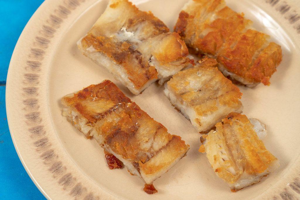 Served fried Alaska Pollock fish on the plate