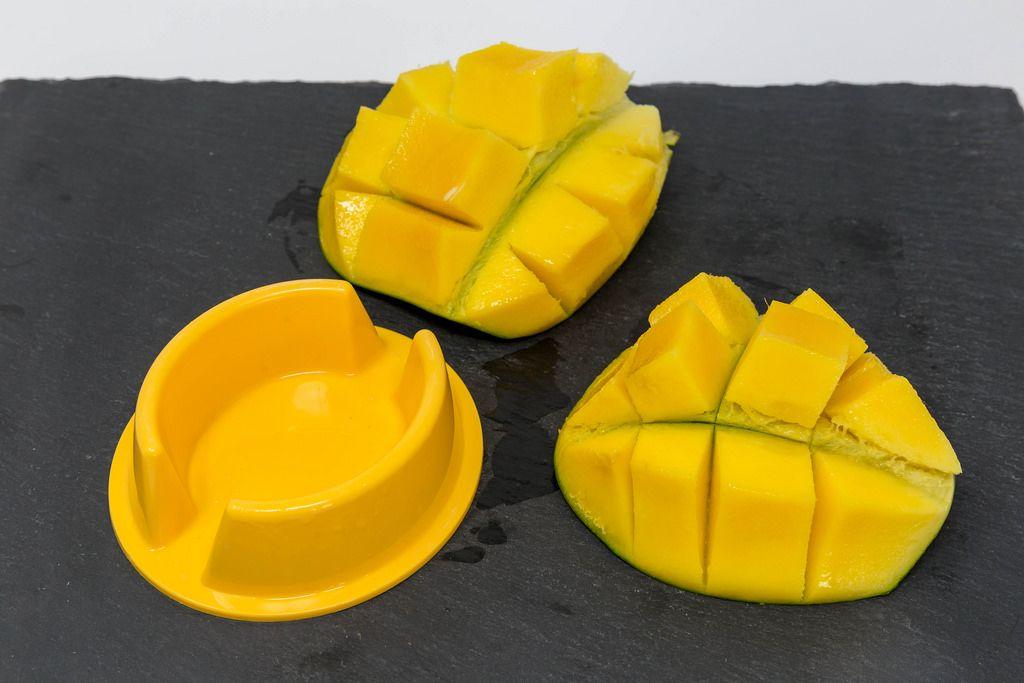 Servierfertige Mangohälften auf schwarzer Schieferplatte