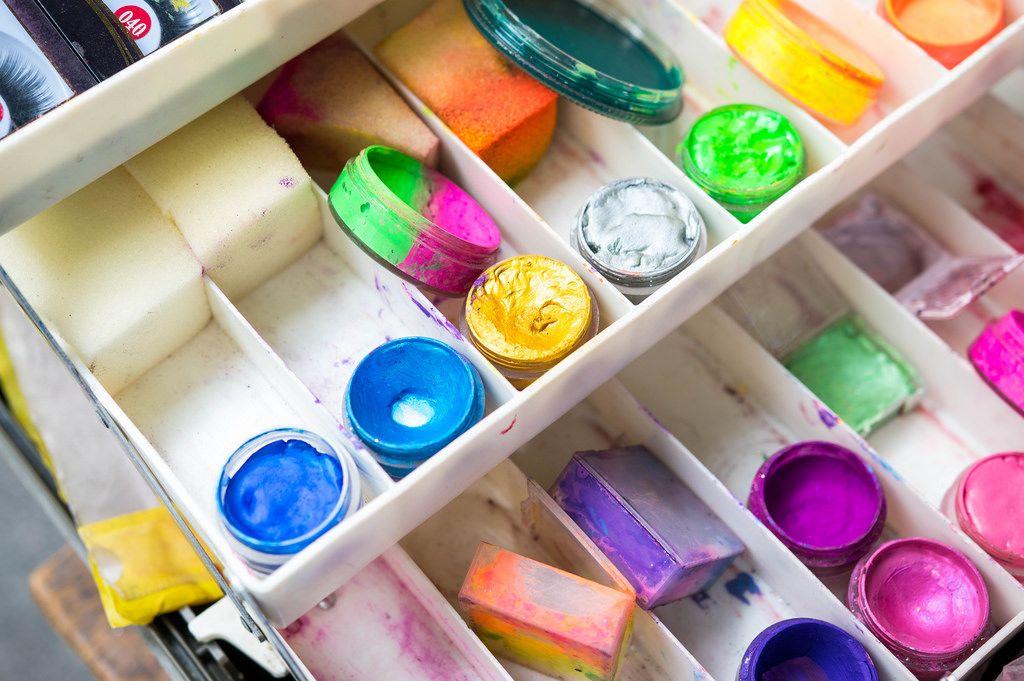 Set aus Theaterschminke mit Schwämmen und Farbtöpfen in blau, gelb, grün und pink in weißer Plastikbox