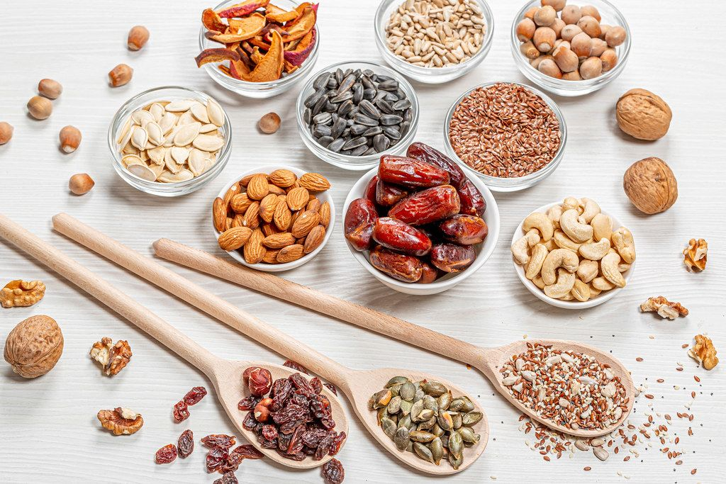 Set nuts, seeds, dried fruits in different bowls and wooden spoons on white wooden background