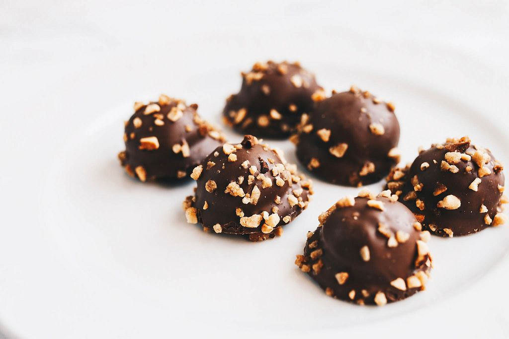 Set of chocolate candy with nuts on top. White background