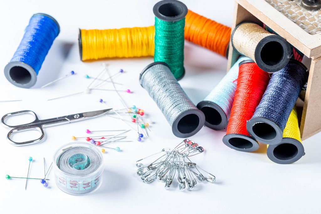Set of colorful threads, needles, pins and scissors with measuring tape