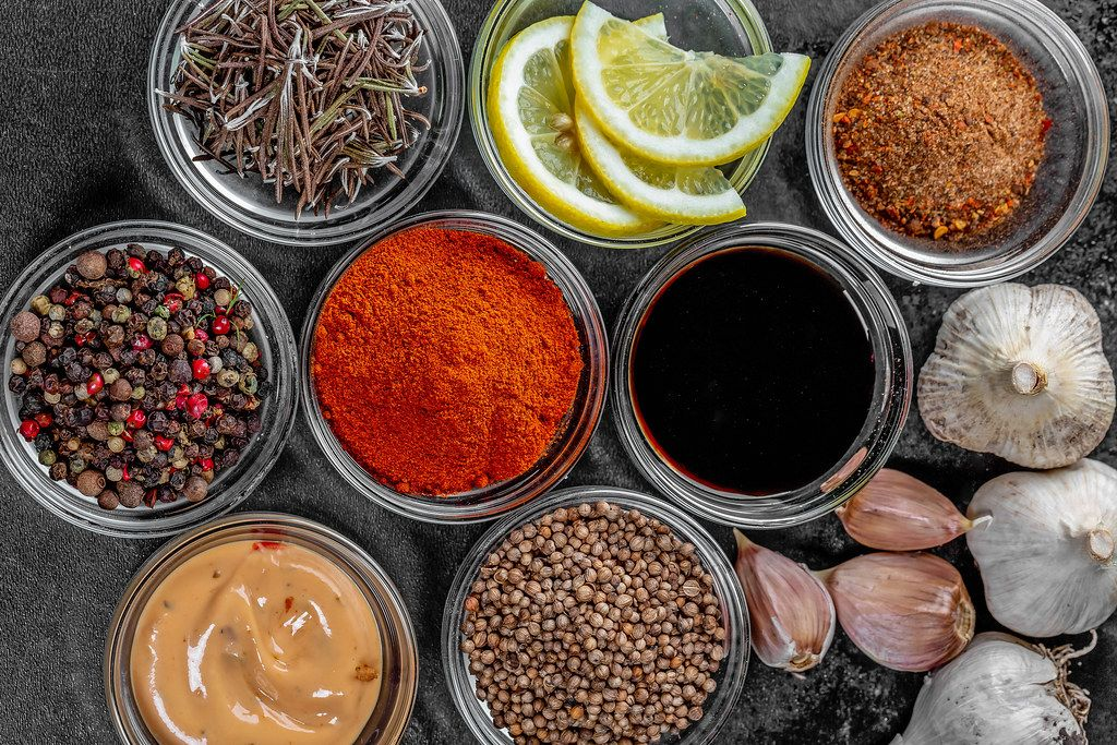 Set of different spices and sauces on a dark background