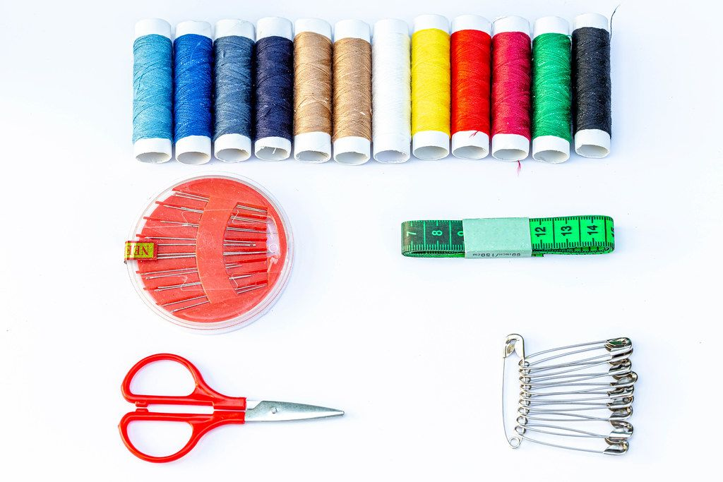 Sewing kits on white background with threads, needles and scissors