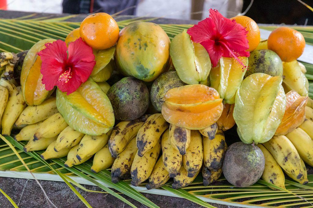 Seychellen-Obst auf Palmenblätter gestapelt, mit Bananen, Mangos, Sternfrucht und Orangen am Anse Source d'Argent Strand auf La Digue