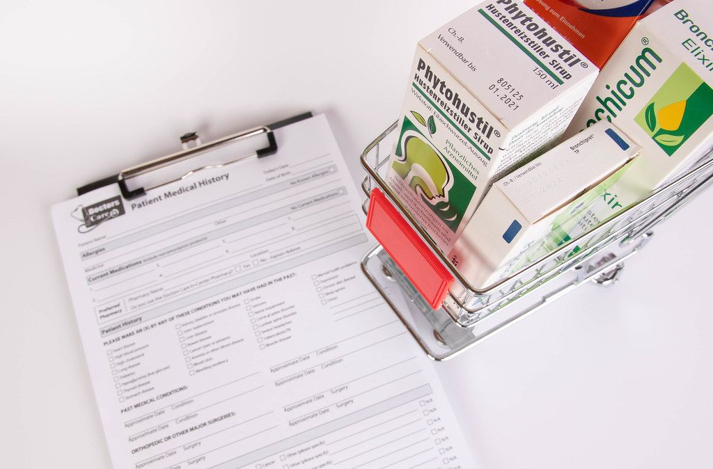 Shopping cart filled with medicines next to a Patient Medical History form
