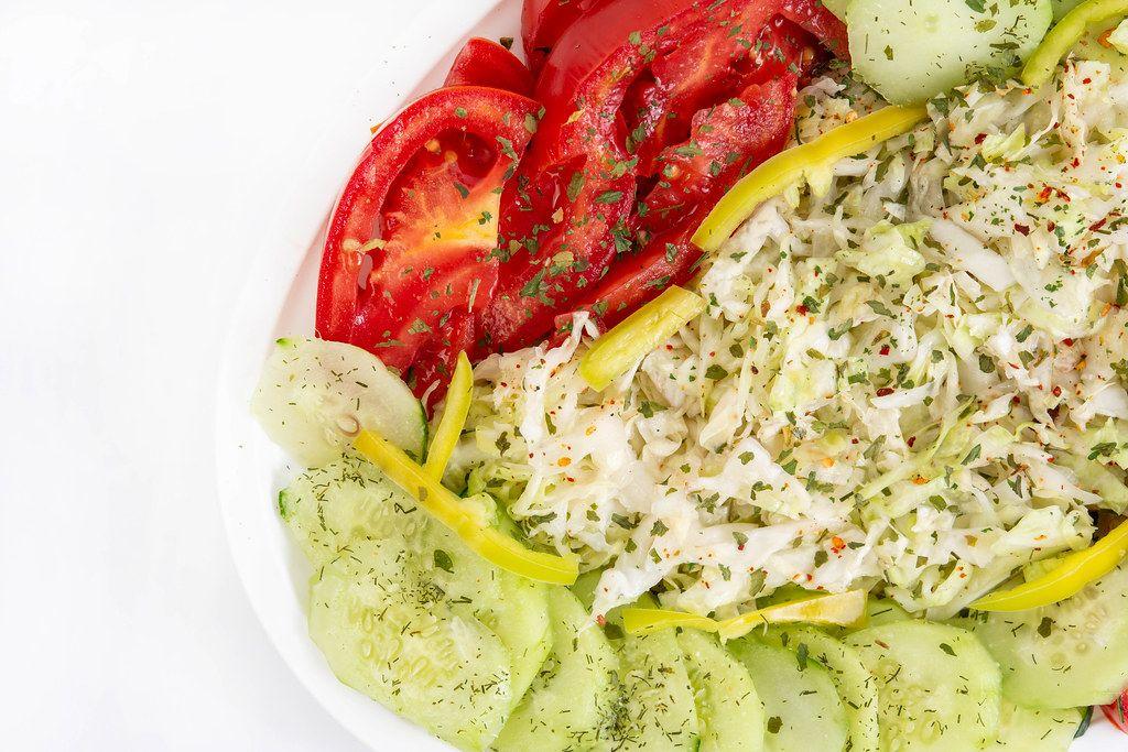 Sicht von oben auf einen bunten Salat mit Gurken, Tomaten und Kohl