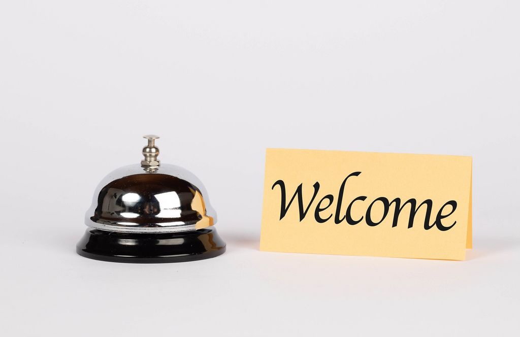 Silberne Hotelglocke neben Schild mit dem Wort WELCOME (Willkommen) vor weißem Hintergrund