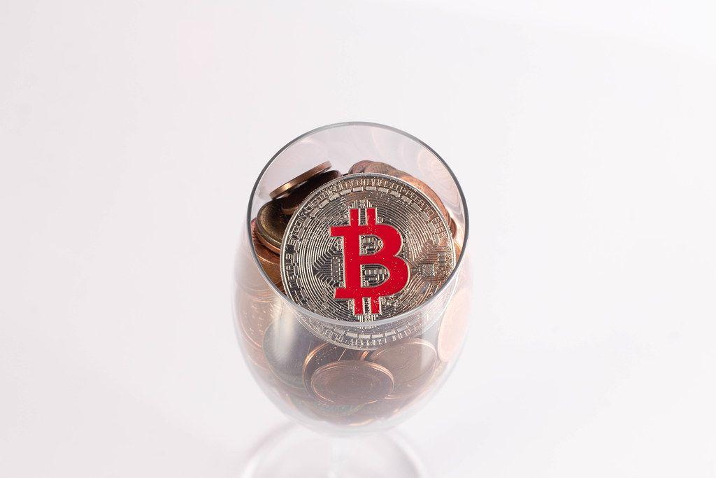 Silberner Bitcoin und Münzen im Champagnerglas