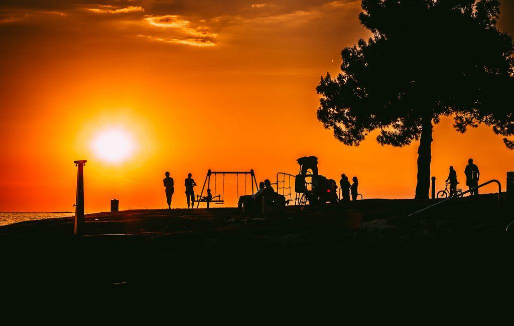 Silhouetten mehrerer Menschen beim Sonnenuntergang