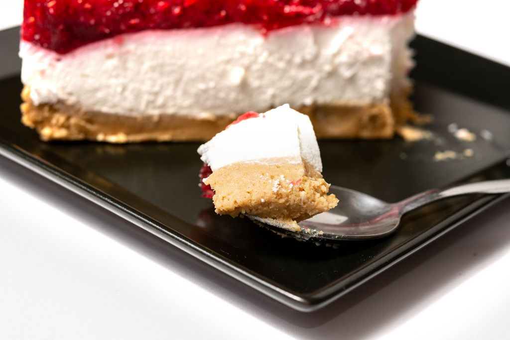 Slice on the spoon of Cheesecake with Raspberry cream