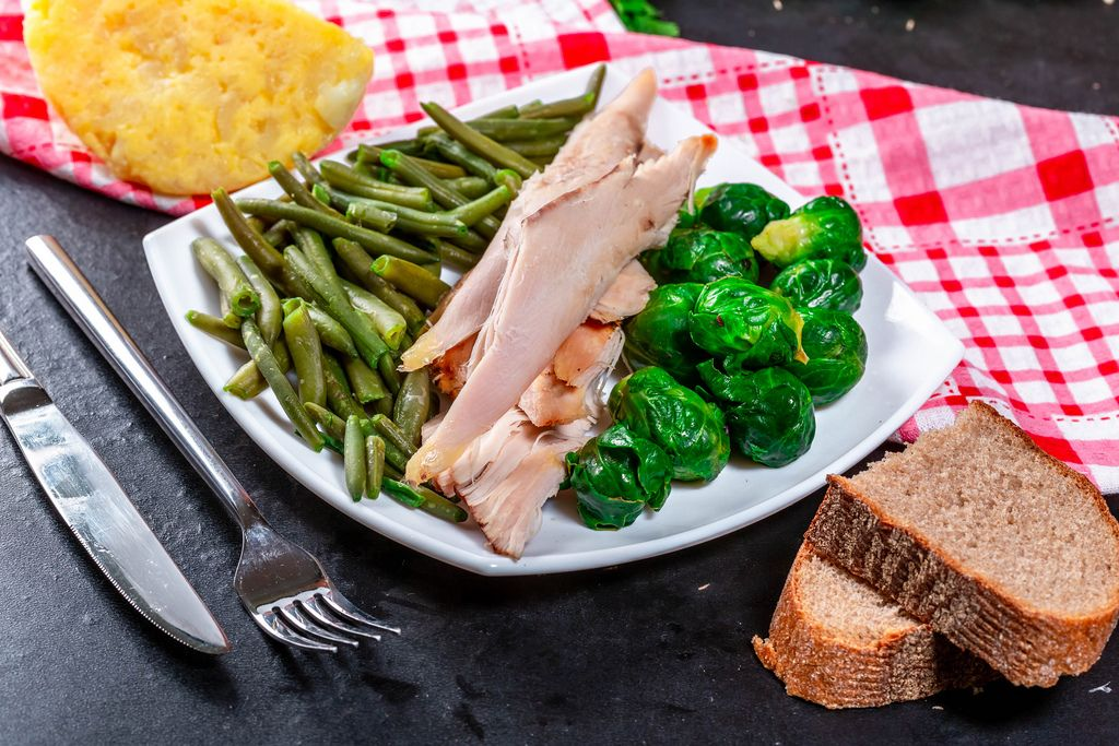 Sliced baked chicken breast with Brussels sprouts and asparagus