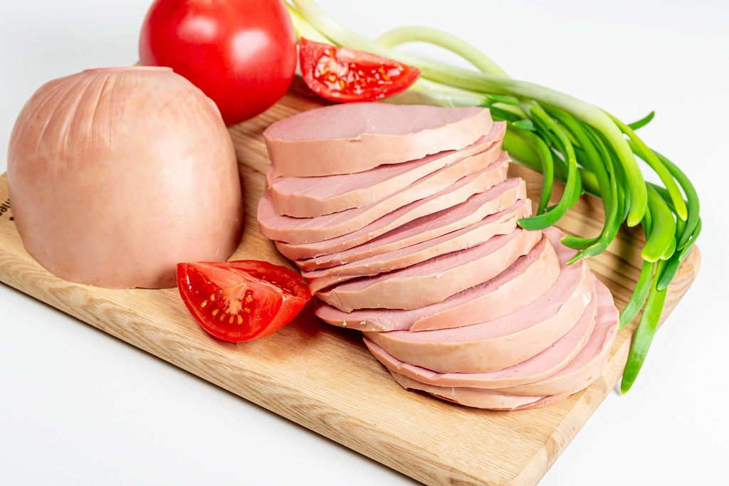 Sliced boiled sausage on a wooden cutting board with tomatoes and green onions