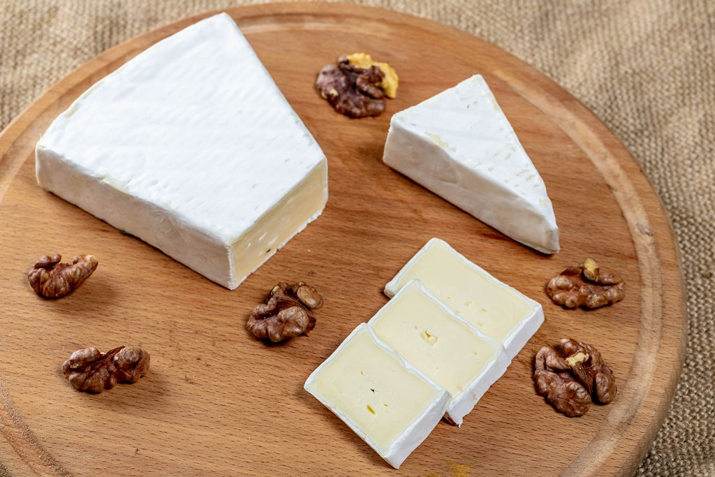 Sliced brie cheese with walnut kernels on a round kitchen Board