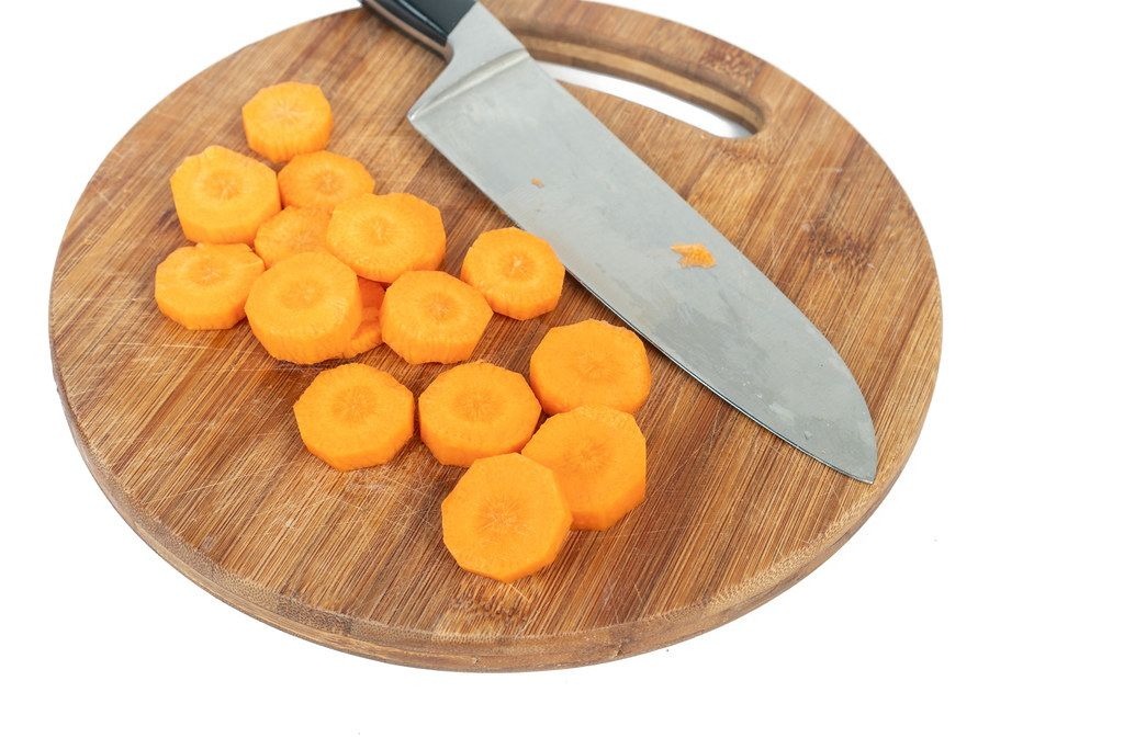 Sliced Carrot on the round wooden board with knife